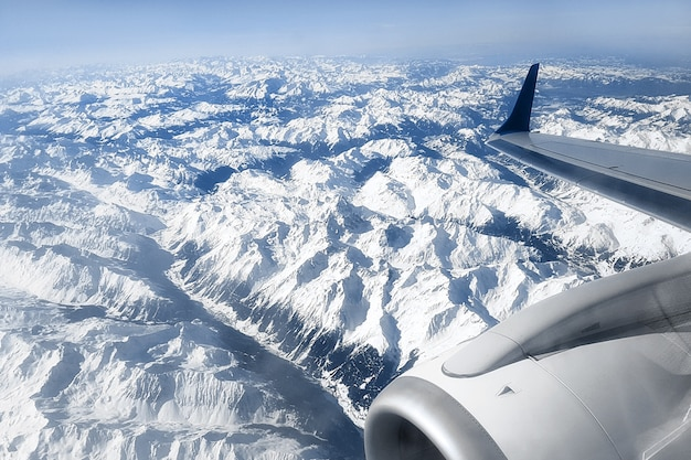 View from the airplane window on the snow-capped peaks of the alpine mountains and the engine of the aircraft