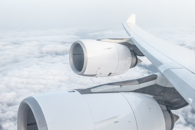 View from airplane window and the wing, over fluffy clouds, flying and traveling concept