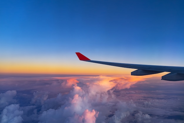 View from airplane window and the wing with sunset sky over fluffy clouds, flying and trav