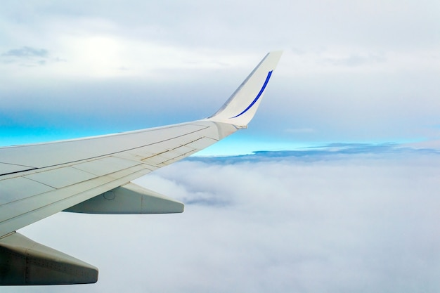 View from airplane window with blue sky and clouds