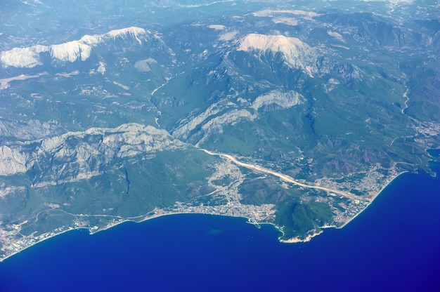 바다, 마을, 산이 있는 비행기 창에서 보기