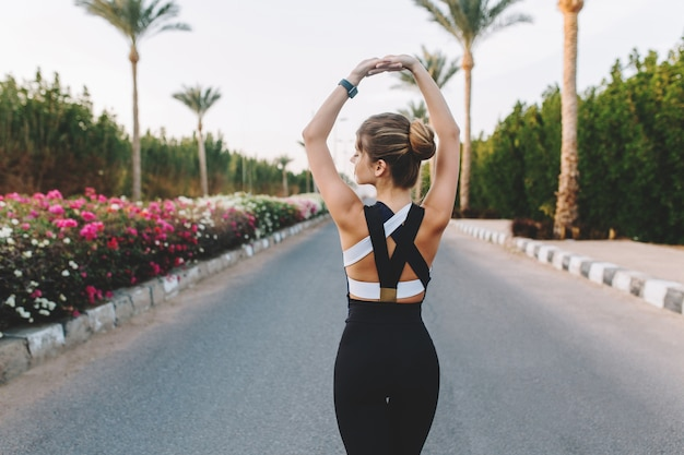 View from back amazing attractive woman in sportswear strecthing on road in tropical city. sunny morning, palm trees, colorful flowers, true emotions, healthy lifestyle, workout, fashionable model