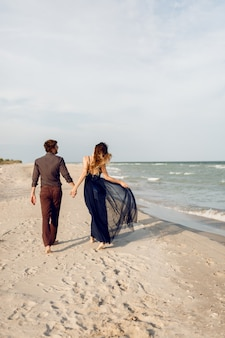 後ろから見たところ。ビーチに沿って歩く愛のエレガントなカップル。ロマンチックな瞬間。白い砂浜と海の波。熱帯の休暇。全高。