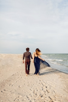 View from back. elegant couple in love walking along the beach. romantic moments. white sand and ocean waves. tropical vacation. full height.
