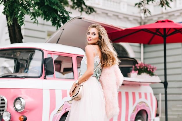 レトロなコーヒー車の背景にチュールスカートの後ろのファッションモデルからの眺め。彼女はカメラに微笑んでいます。