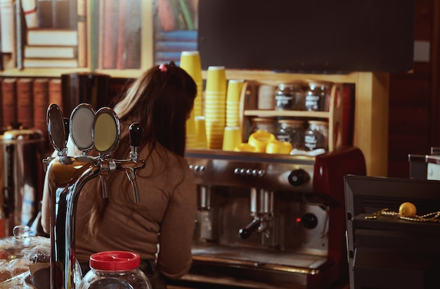 View from the back of female barista preparing coffee in professional coffee machine