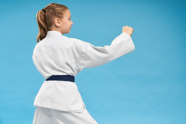 View from back of girl doing karate on isolated background