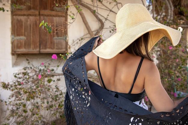 Una vista dal retro di una ragazza che indossa un cappello con un mantello davanti a un muro coperto da un vecchio albero riccio.