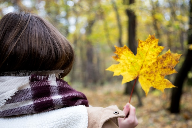 View from the back of a girl who is wrapped in a scarf or rug and holds a beautiful maple yellow leaf in her hand