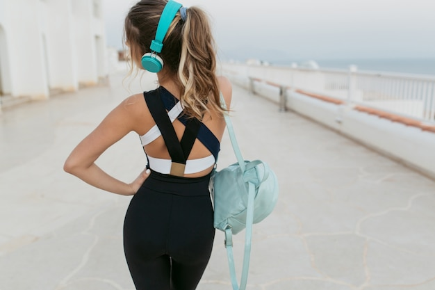 View from back joyful amazing woman in sportswear, with long curly hair listening to music through headphones, walking on seafront. cheerful mood, fitness outside, fashionable model