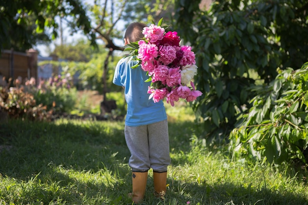 View from the back of little boy in his hands a large bouquet of beautiful peony flowers