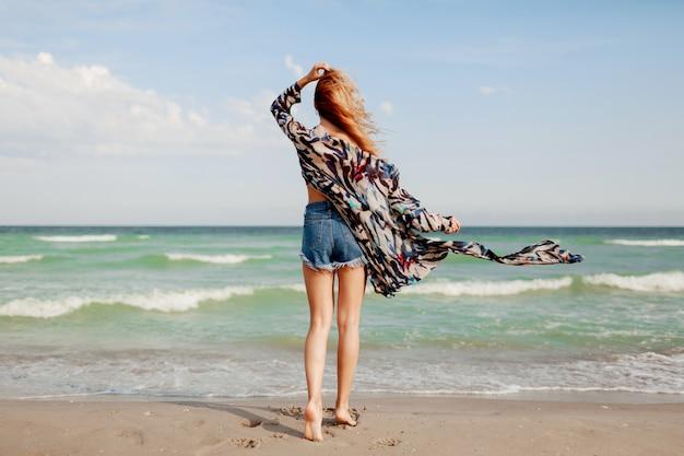 Вид сзади беззаботной грациозной женщины с удивительными рыжими волосами, бегающими по пляжу