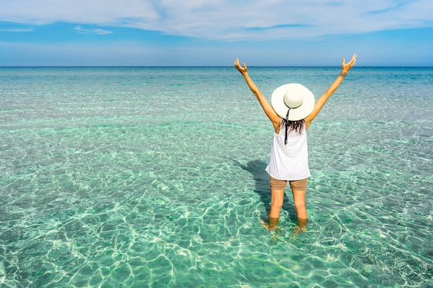 休暇中に大きな白い帽子をかぶった流行に敏感な認識できない幸せな若い女性の後ろからの眺め