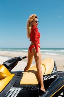熱帯の砂浜でセクシーな日焼けした女性のビキニモデルの後ろからの眺め。ウォータースクーターで水着姿のグラマーガール。