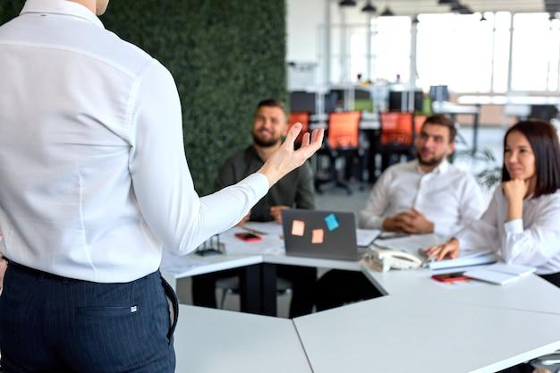 同僚にスピーチをし、話をしているフレンドリーで素敵なビジネスリーダーマネージャーを後ろから見る