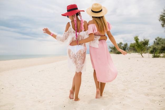 Вид сзади на двух красивых стильных женщин на пляже в отпуске, летний стиль, модная тенденция, в соломенных шляпах, модная тенденция, розовое и кружевное платье, сексуальный наряд