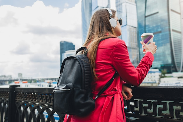 ピンクのコート、サングラス、バックパックとヘッドフォンで音楽を聞いてコーヒーを飲みながら通りを歩いてジーンズで流行に敏感な若い女性を後ろから見る