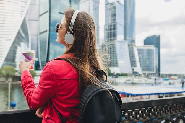 Вид сзади на молодую хипстерскую женщину в розовом пальто, джинсах, идущих по улице с рюкзаком и кофе, слушающих музыку в наушниках