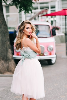 ピンクのレトロな車の背景に長いブロンドの髪を持つスタイルの女の子を後ろからピンからの眺め。彼女は唇を見ながら指を離さずにカメラを見ています。