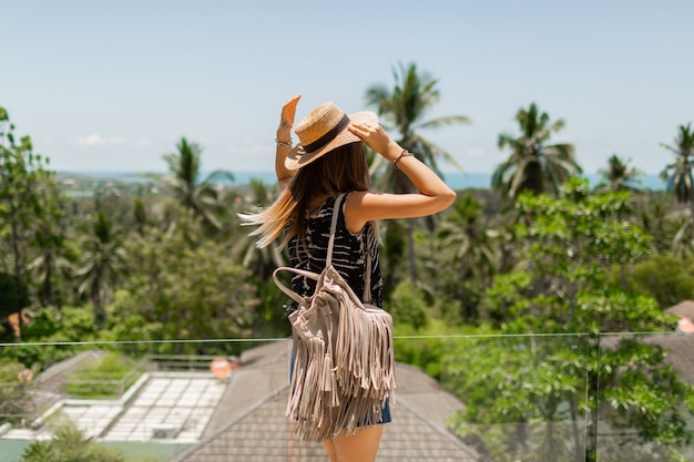 View from back of traveling woman in straw hat enjoying amazing tropical landscape