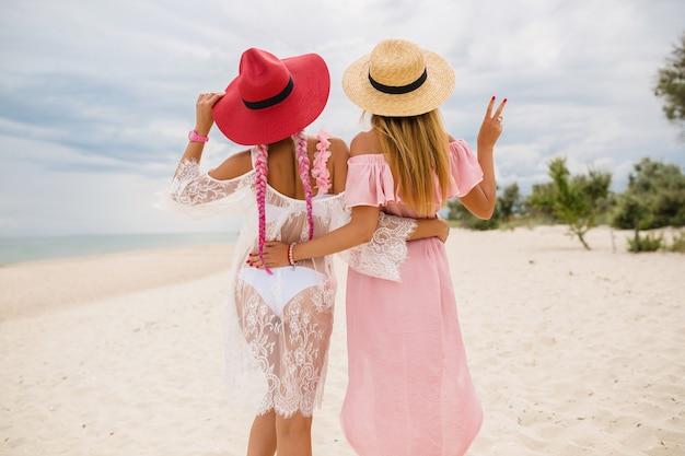 Vista dal retro su due belle donne alla moda in spiaggia in vacanza, stile estivo, tendenza della moda, cappelli di paglia con indosso, tendenza della moda, abito rosa e pizzo, vestito sexy