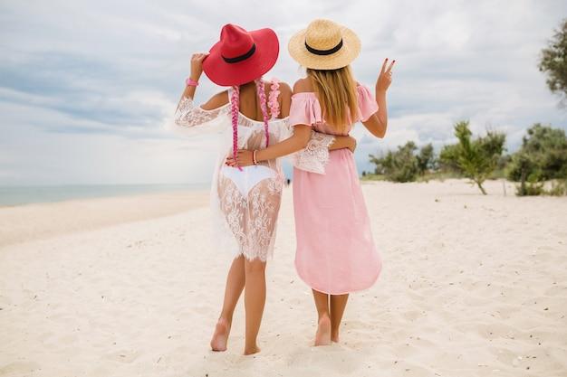 Vista dal retro su due belle donne alla moda in spiaggia in vacanza, stile estivo, tendenza della moda, indossare cappelli di paglia, tendenza della moda, abito rosa e pizzo, vestito sexy
