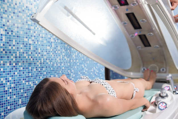 View from back of woman lying in tanning bed in spa
