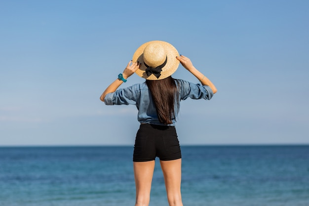 View from back. woman in straw hat, with figure looking on the sea.