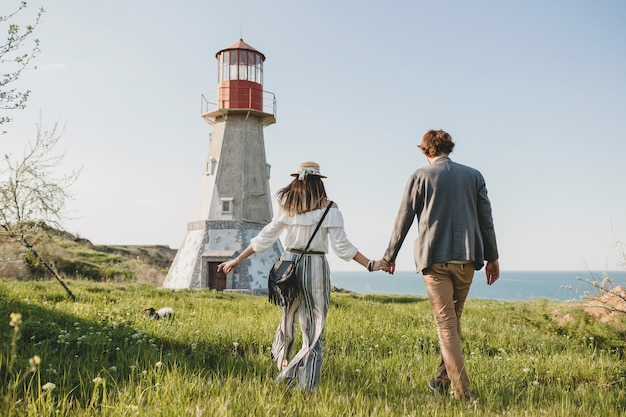 View from back on young couple hipster indie style in love walking in countryside, holding hands, lighthouse on background, warm summer day, sunny, bohemian outfit, hat