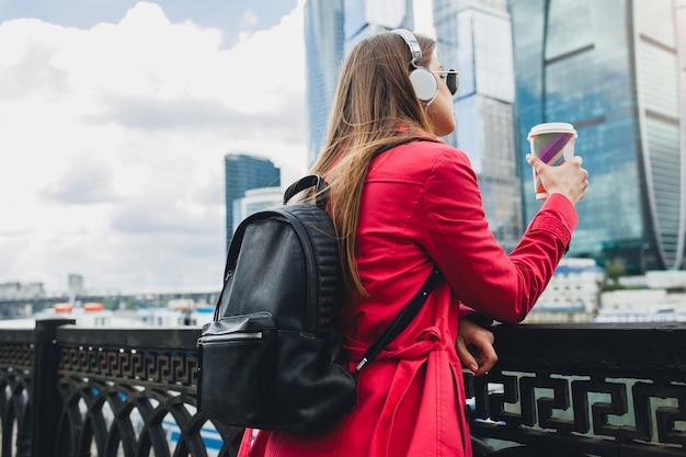 Vista dal retro su giovane donna hipster in cappotto rosa, jeans che camminano in strada con zaino e caffè ascoltando musica in cuffia, indossando occhiali da sole