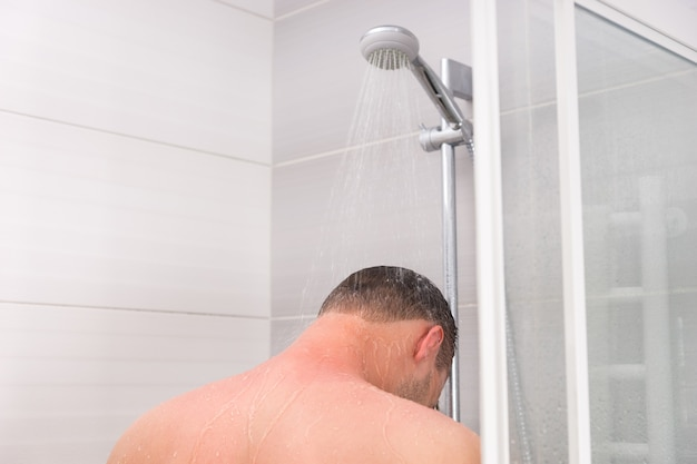 View from the back on a young man taking a shower and standing under flowing water in the modern tiled bathroom