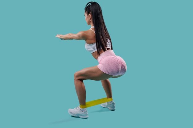 View from the back of young sporty woman in white top and pink sports shorts doing squatting with elastic fitness band isolated