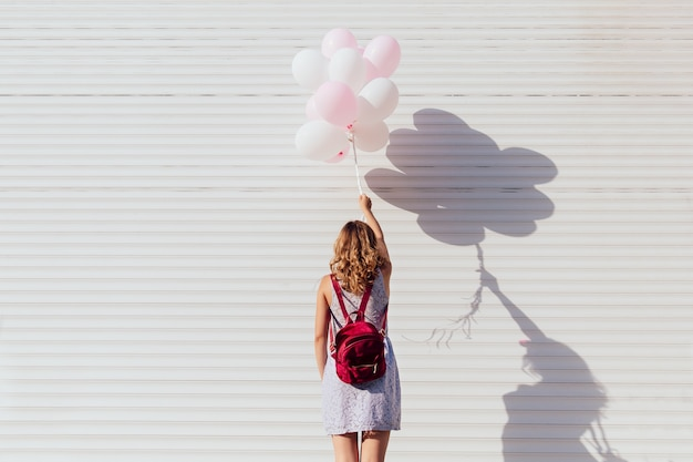 View from back of young woman with backpack, holding air balloons