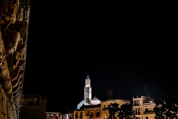 View from the bari castle of the bell tower of its cathedral during the night.