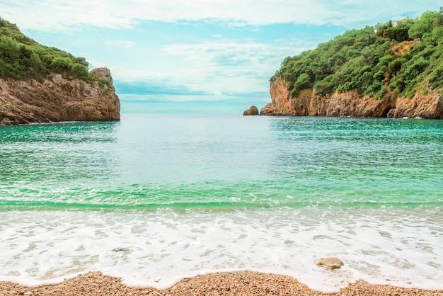 코르푸 섬, 그리스에 paleokastritsa에서 맑은 물과 놀라운 베이 해변에서 볼 수 있습니다. 나무와 두 개의 바위의 아름 다운 풍경입니다.