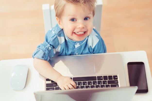 2歳の子供の後ろからの眺めコンピューターまたはラップトップで作業および印刷