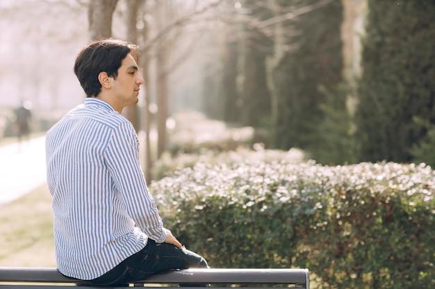 공원에서 벤치에 앉아 남자의 뒤에서 볼 수 있습니다. 고품질 사진