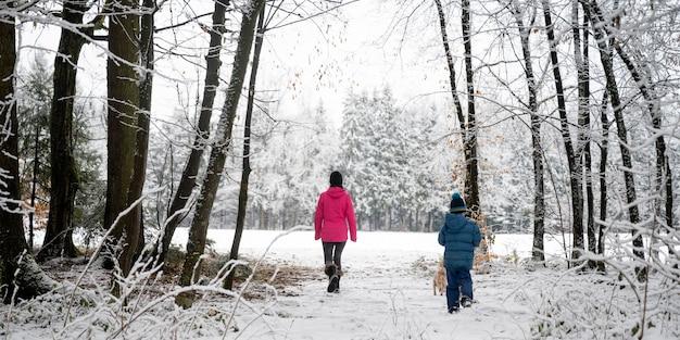 주변의 귀여운 작은 강아지와 함께 아름다운 눈 덮인 숲에서 산책하는 어머니와 아들의 뒤에서 볼 수 있습니다.