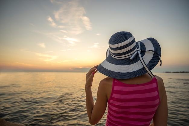 파란색과 흰색 박탈 밀짚 모자가 거리를 들여다보고 해안에 앉아있는 여자의 뒤에서보기