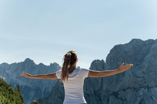 팔 벌리고 알프스의 경치를 즐기는 삶을 즐기는 젊은 여성 등산객의 뒤에서 볼 수 있습니다.