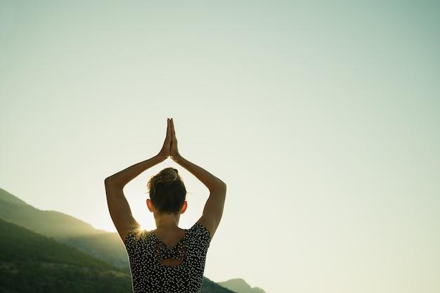 그녀가 일출에 아침 요가 운동을 할 때 그녀의 팔을 그녀의 머리 위로 결합하여 아사나 포즈를 취하는 젊은 여성의 뒤에서 볼 수 있습니다.
