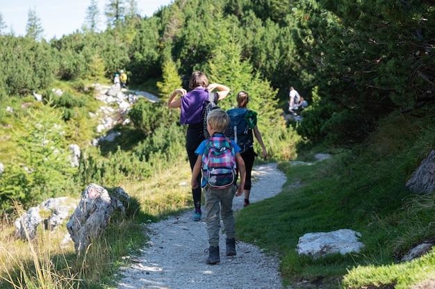 Вид сзади взрослых и детей на пешие прогулки, прогулки по горной тропе с рюкзаками