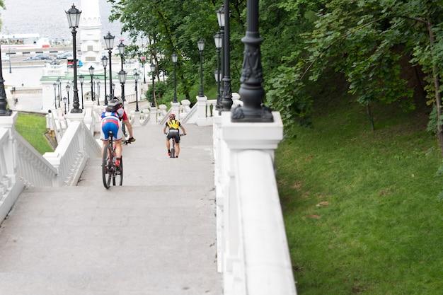 Вид сзади на спускающихся по ступеням велосипедистов