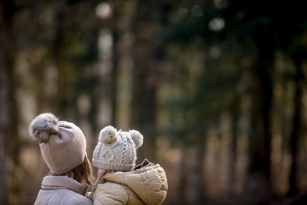 Вид сзади на мать, держащую своего ребенка, обе в теплых шляпах на улице в лесной зоне
