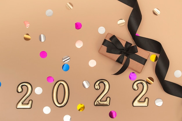 View from above. beige background with star confetti, gift box with black ribbon and golden numbers. merry christmas and happy new year 2022 greeting card.