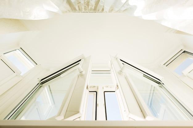 白い透明なカーテンが付いているプラスチックビニールの窓の下からの眺め