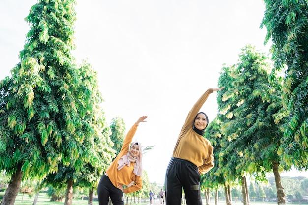 公園で運動する前に、ベールに身を包んだ2人の女の子の下から見たところ、腕を上に上げ、体を横に傾けて腕を伸ばしています。