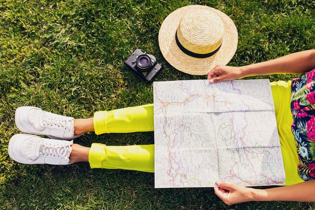 View from above of black woman hands holding map, traveler with camera having fun in park summer fashion style, colorful hipster outfit, sitting on grass