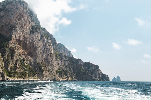 View from the boat on capri island coast and faraglioni oceanic rock formation.