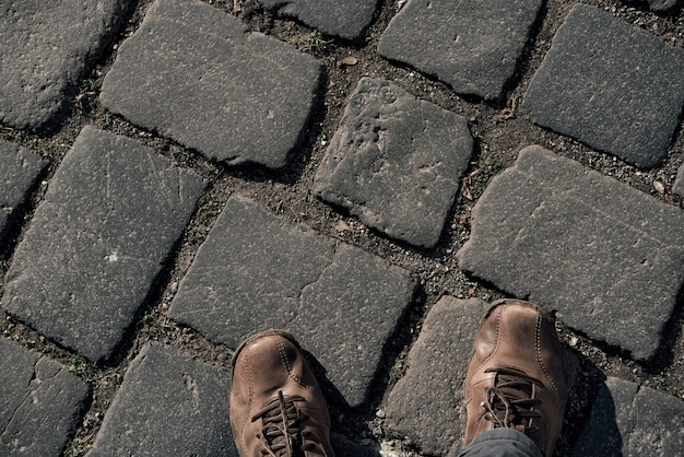 View from above on brown boots on cobblestone pavement